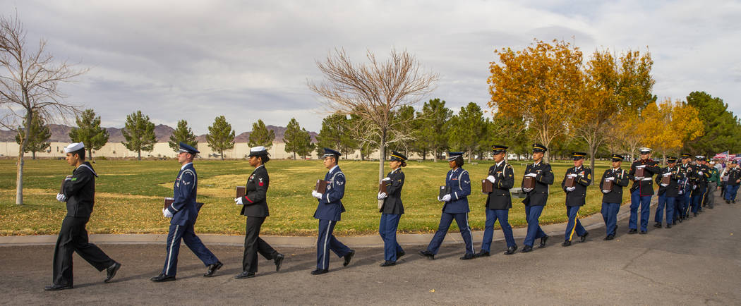 Military Honor Guard members march with urns to awaiting burial plots during the third Missing ...