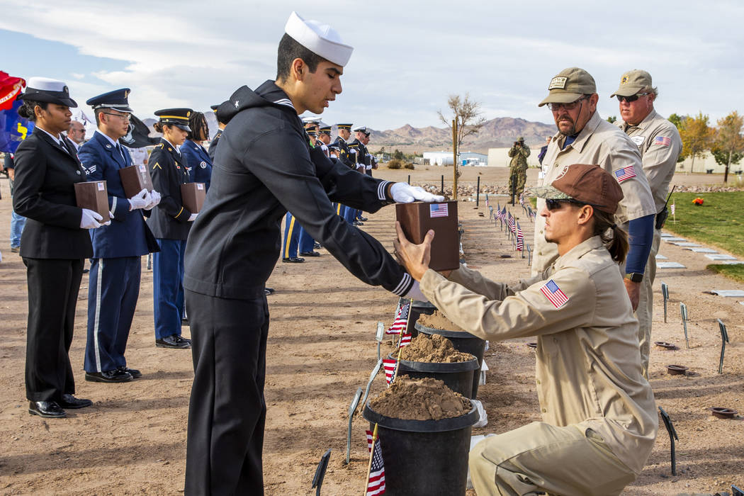 Seaman Alex Ramirez presents an urn for burial to Brandon Hall with the Southern Nevada Veteran ...