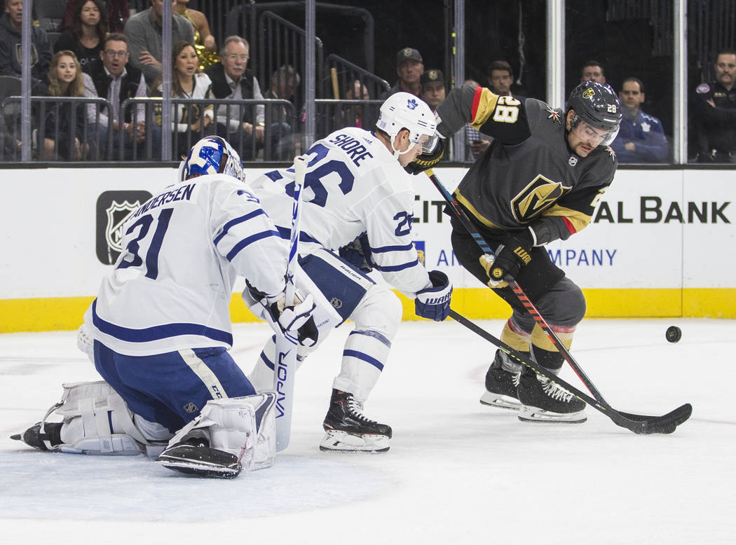 Vegas Golden Knights left wing William Carrier (28) fights for a loose puck with Toronto Maple ...