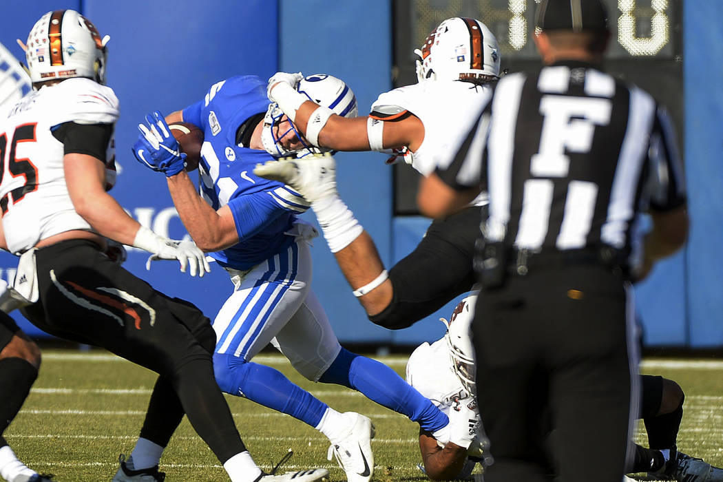 BYU wide receiver Talon Shumway (21) gets his head wrenched by Idaho State defensive back Manas ...