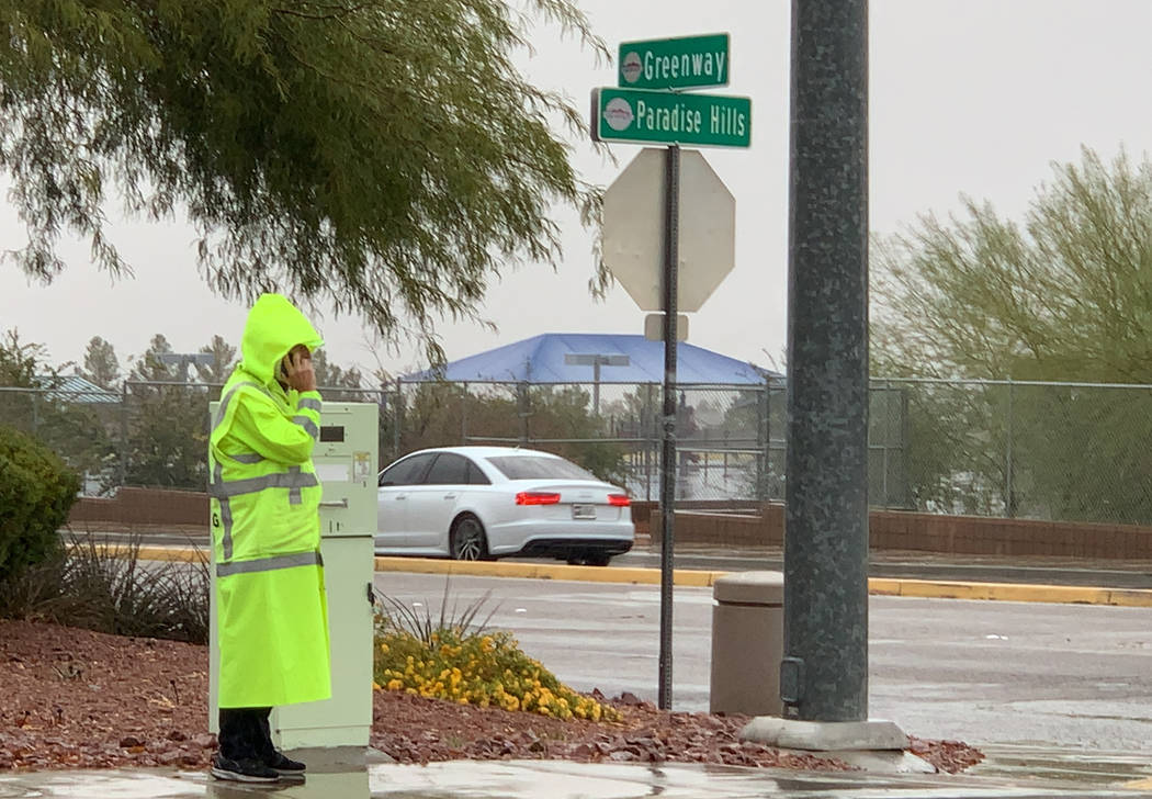 A crossing guard talks on the phone while standing in the rain on a street corner between Smile ...