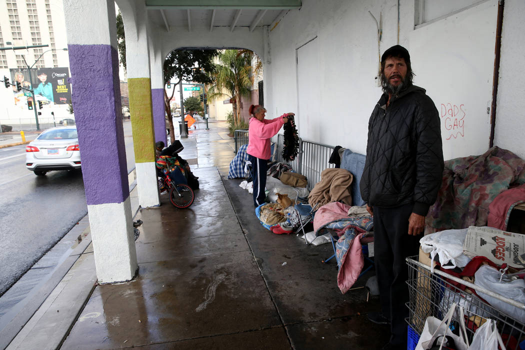 Darrell Leis, right, and Nancy Williams, 53, take shelter from the rain on Main Street near Bri ...