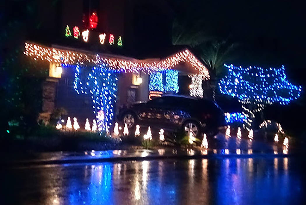 Water from early Wednesday, Nov. 20, 2019, rainfall reflects the Christmas lights at a home on ...