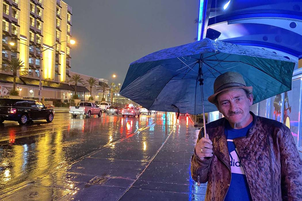 Jimmy James is protected from the light rain as he waits for a bus at Tropicana