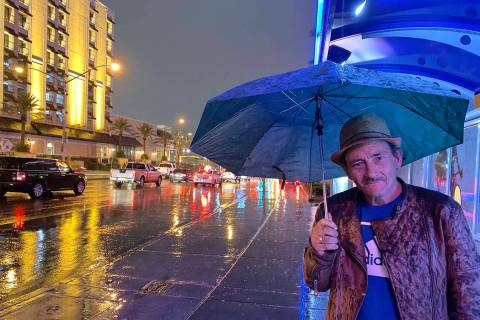 Jimmy James uses an umbrella to protect himself from rain as he waits for a bus about 5 a.m. We ...
