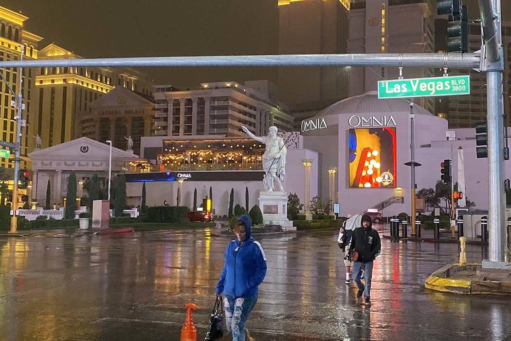 Pedestrians cross the Las Vegas Strip near Caesars Palace in the rain, Wednesday, Nov. 20, 2019 ...