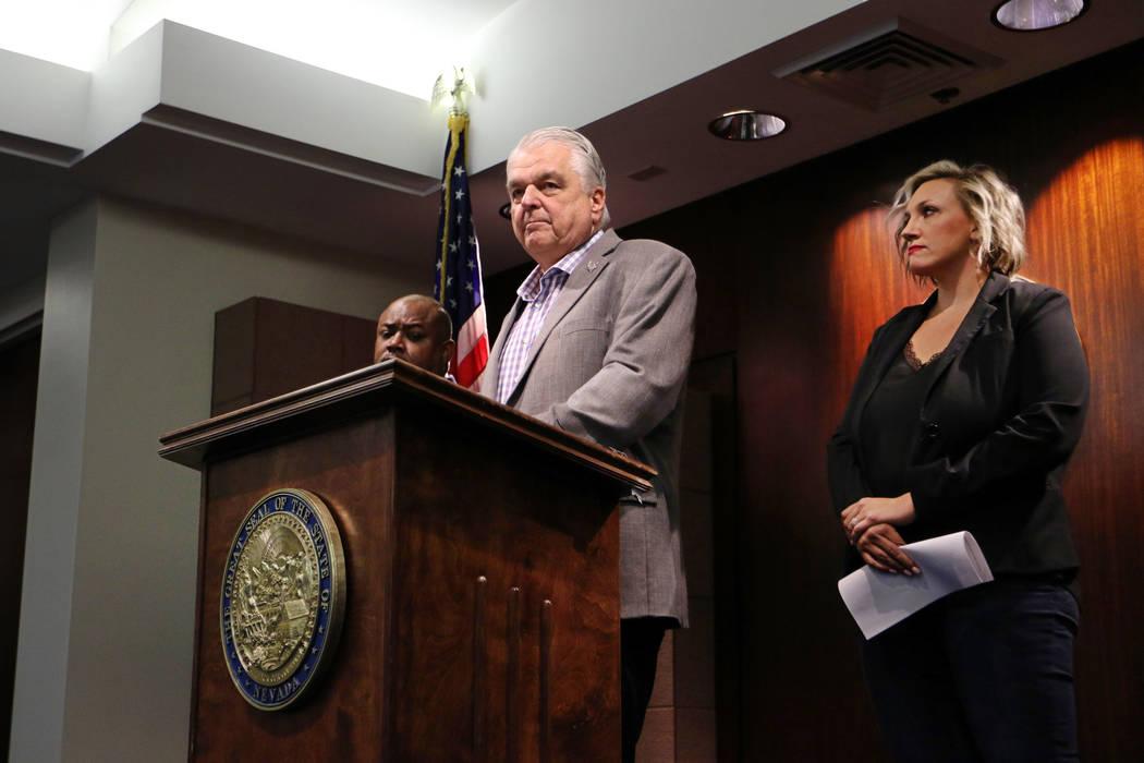 In this Aug. 23, 2019, file photo, Nevada Gov. Steve Sisolak, center, with Majority Leader Nico ...