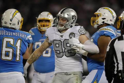 Oakland Raiders defensive end Maxx Crosby (98) reacts next to Los Angeles Chargers center Scott ...