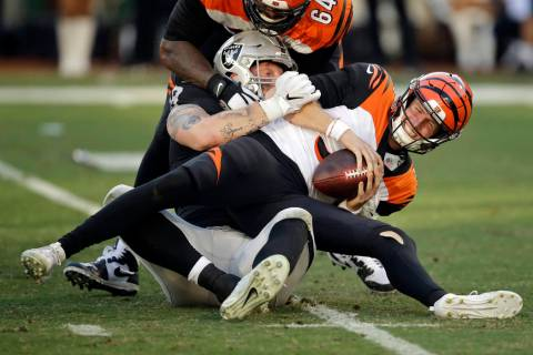 Cincinnati Bengals quarterback Ryan Finley, front, is sacked by Oakland Raiders defensive end M ...