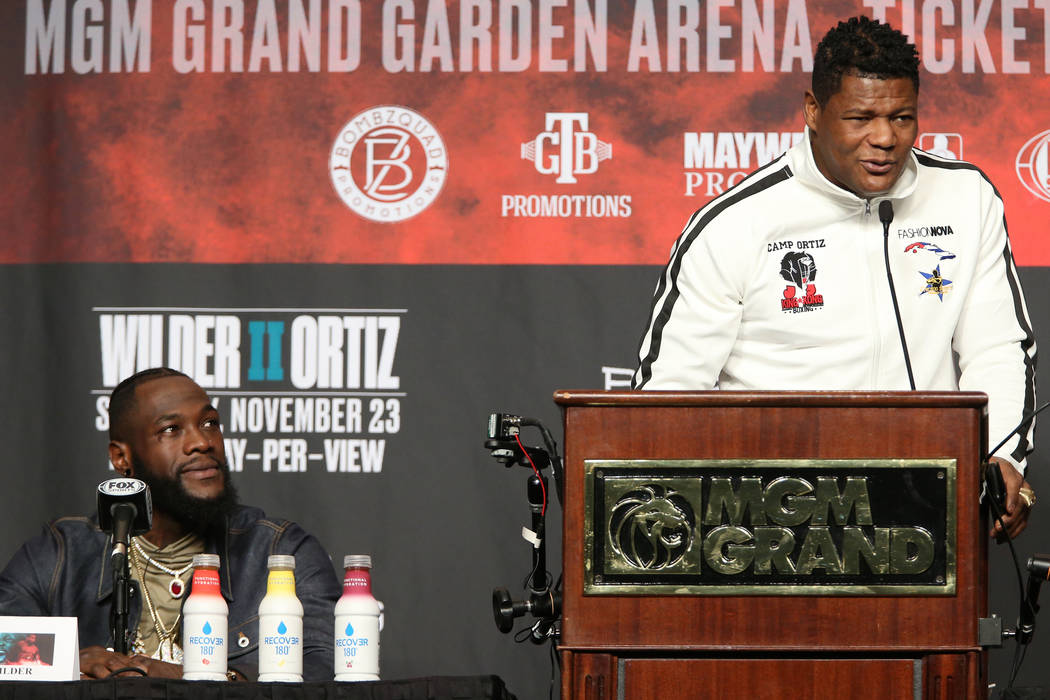 Luis Ortiz, right, speaks during a press conference with his upcoming boxing opponent Deontay W ...
