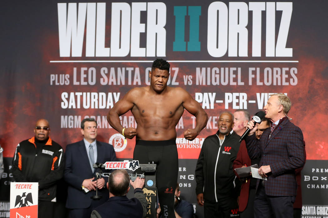 Luis Ortiz stands on the scale during a weigh-in at the MGM Grand Garden Arena in Las Vegas, Fr ...