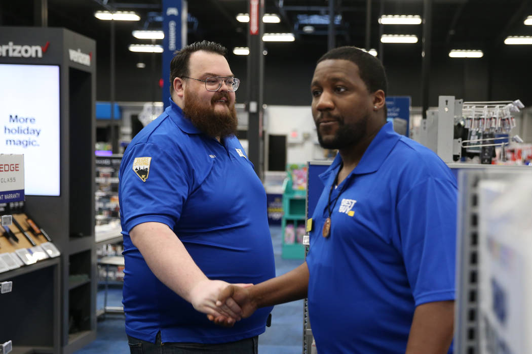 Sales manager Michael Isbell, left, shakes hands with sales consultant T.J. Gardner during a tr ...