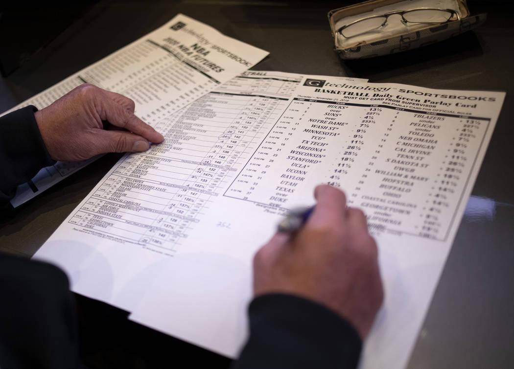 A gambler places a bet at the Palms sportsbook on Thursday, Nov. 21, 2019, in Las Vegas. (Ellen ...