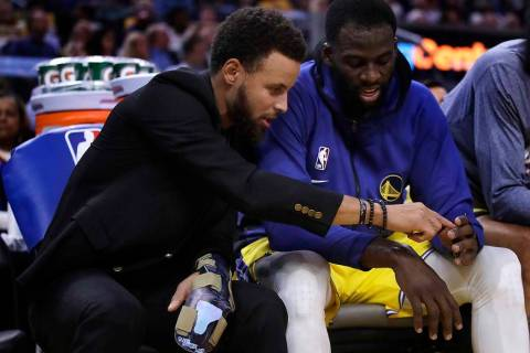Golden State Warriors' Stephen Curry, left, points to the fingers of teammate Draymond Green du ...