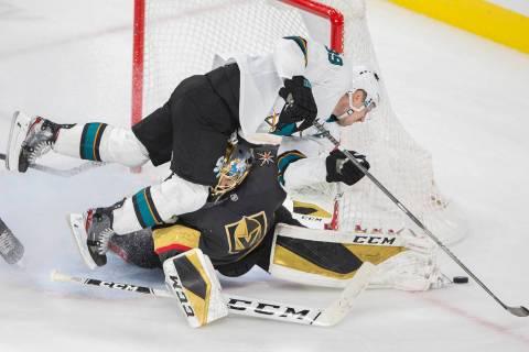 San Jose Sharks center Logan Couture (39) collides with Vegas Golden Knights goaltender Marc-An ...