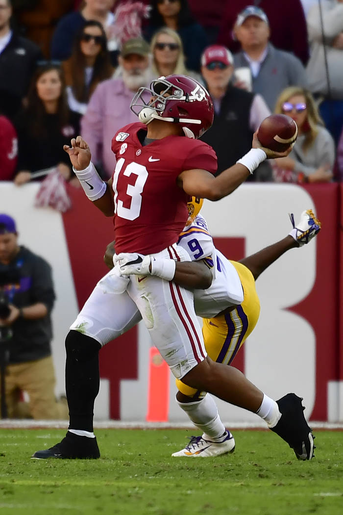 Alabama quarterback Tua Tagovailoa (13) is hit by LSU safety Marcel Brooks (9) as he throws a p ...