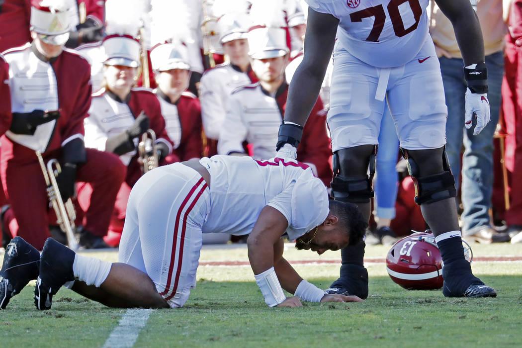 Alabama sive lineman Alex Leatherwood (70) checks on quarterback Tua Tagovailoa (13) after he w ...