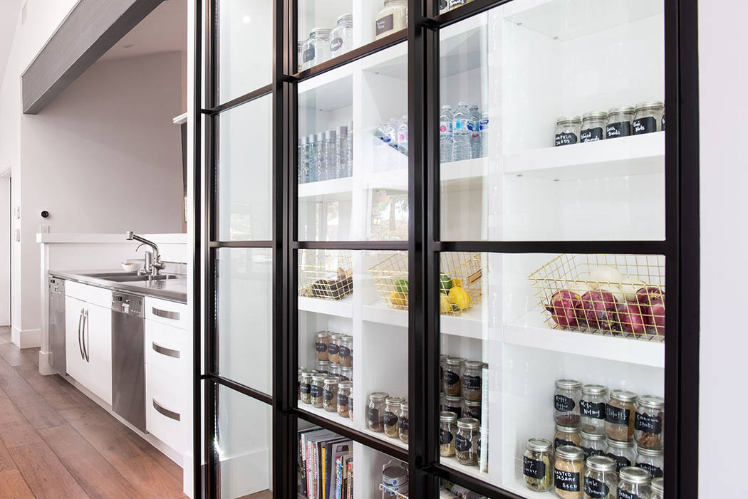 The kitchen showcases an expansive custom pantry with glass doors. (Simply Vegas)