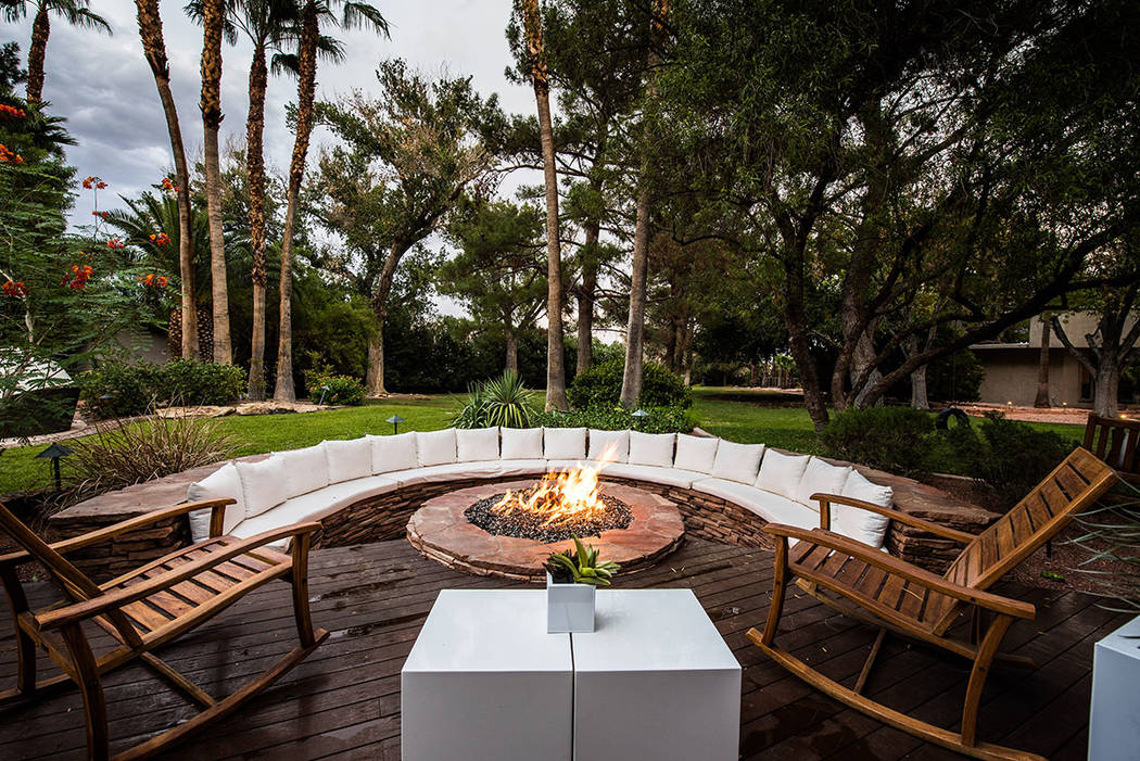 The main house features a large couch and fire pit in lush landscaping. (Simply Vegas)