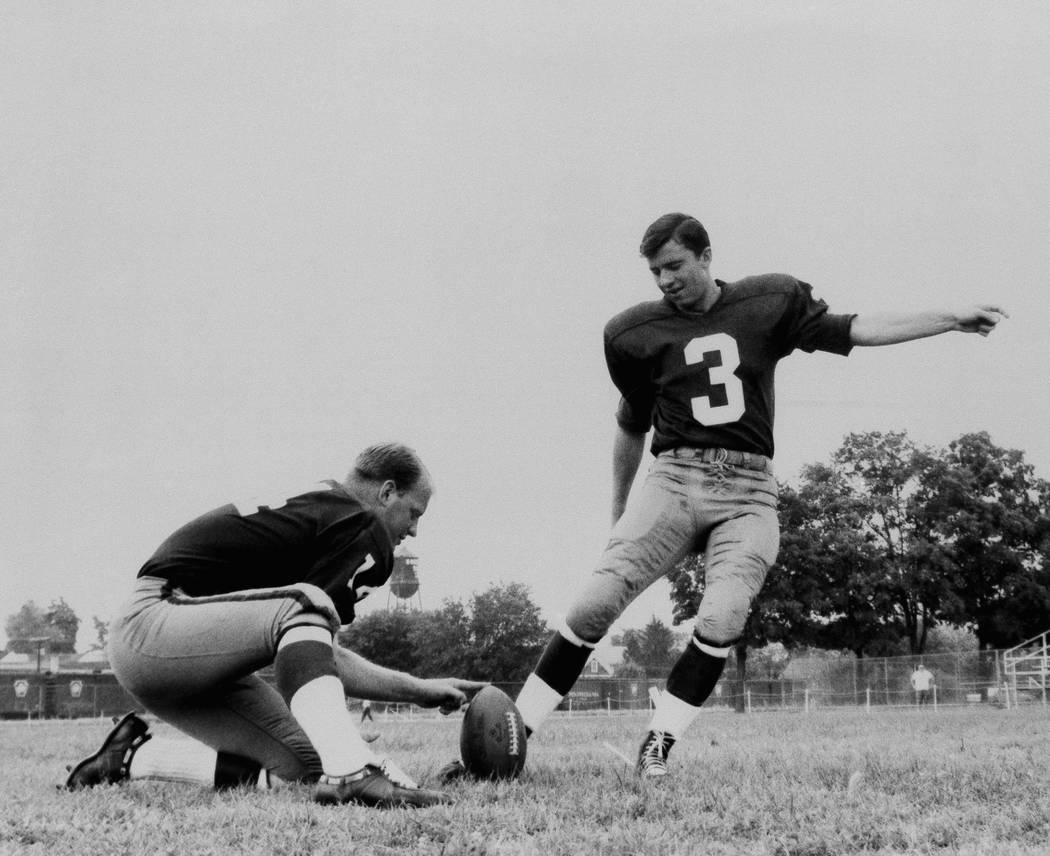 Football players Charlie Gogolak, Kicking with Dick Shine holding, 1966. (AP Photo).