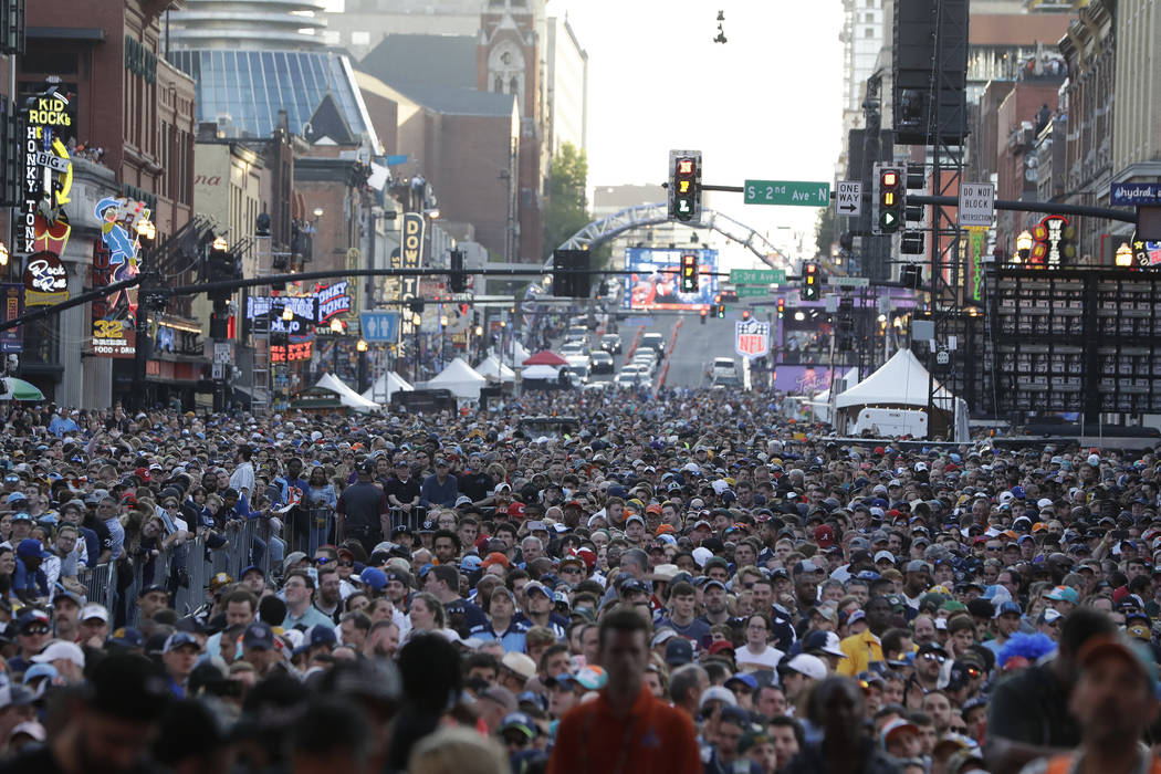 Fans watch ther main stage during the second round of the NFL football draft, Friday, April 26, ...