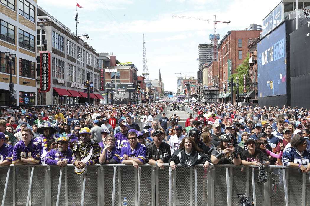 Fans line Broadway before the start of Day 3 of the NFL football draft, in Nashville, Tenn. on ...