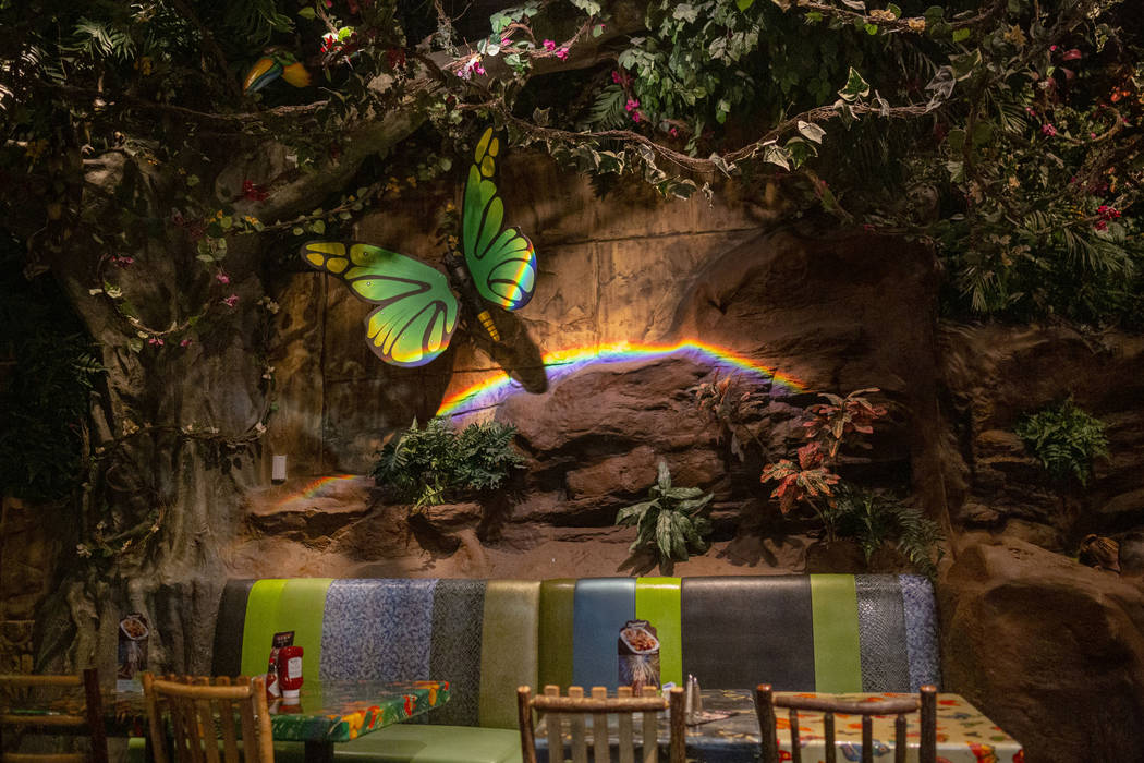 Dining tables covered by plants and mechanical animals in the Rainforest Cafe in the Miracle Mi ...