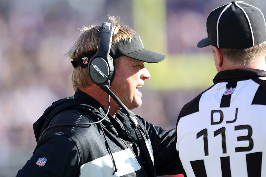 Oakland Raiders head coach Jon Gruden discusses a penalty call with down judge Danny Short (113 ...