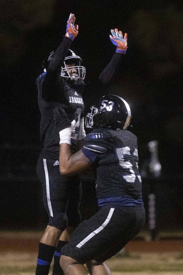 Desert Pines' Tiaoalii Savea (53) lifts up Deandre Moore (2) after Moore scored a touchdown aga ...