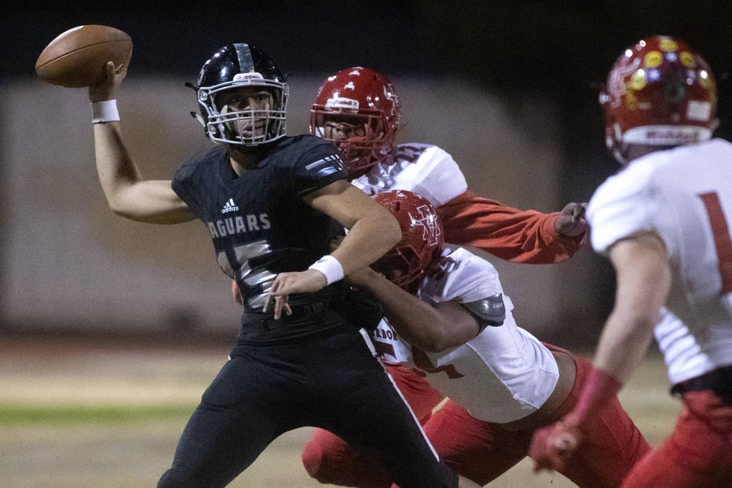 Desert Pines' quarterback Rjay Tagataese (15) looks to throw the ball as Arbor View's Zavier Al ...