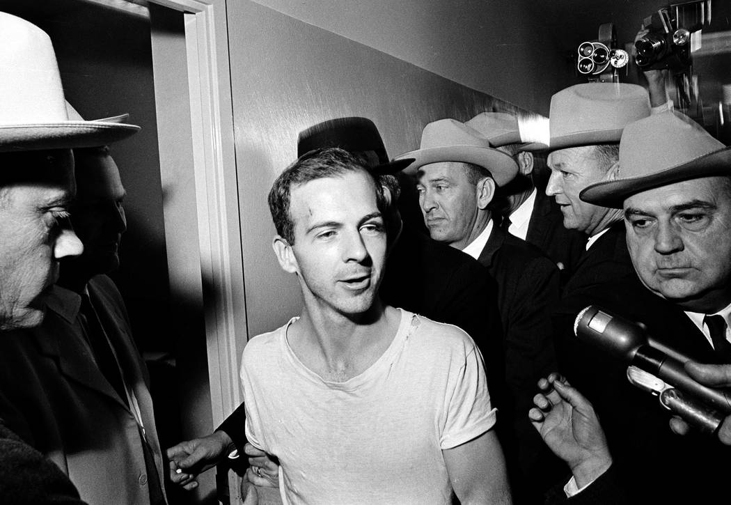 In this Nov. 23, 1963 file photo, surrounded by detectives, Lee Harvey Oswald talks to the pres ...