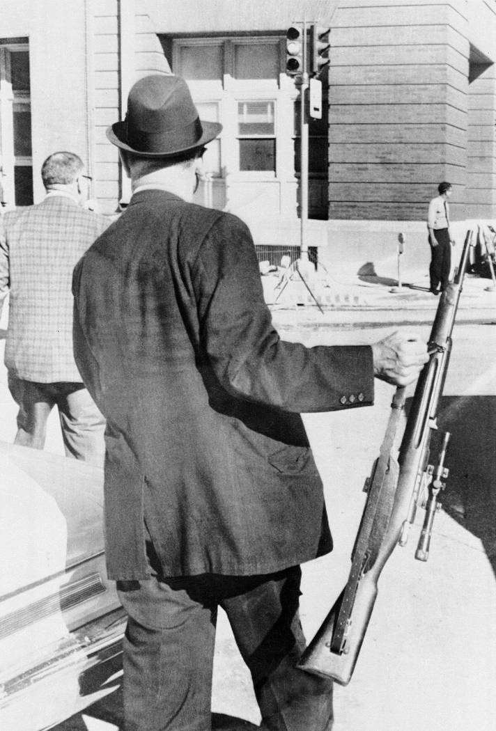 An unidentified plainclothes police officer carries the rifle used in the assassination of Pres ...