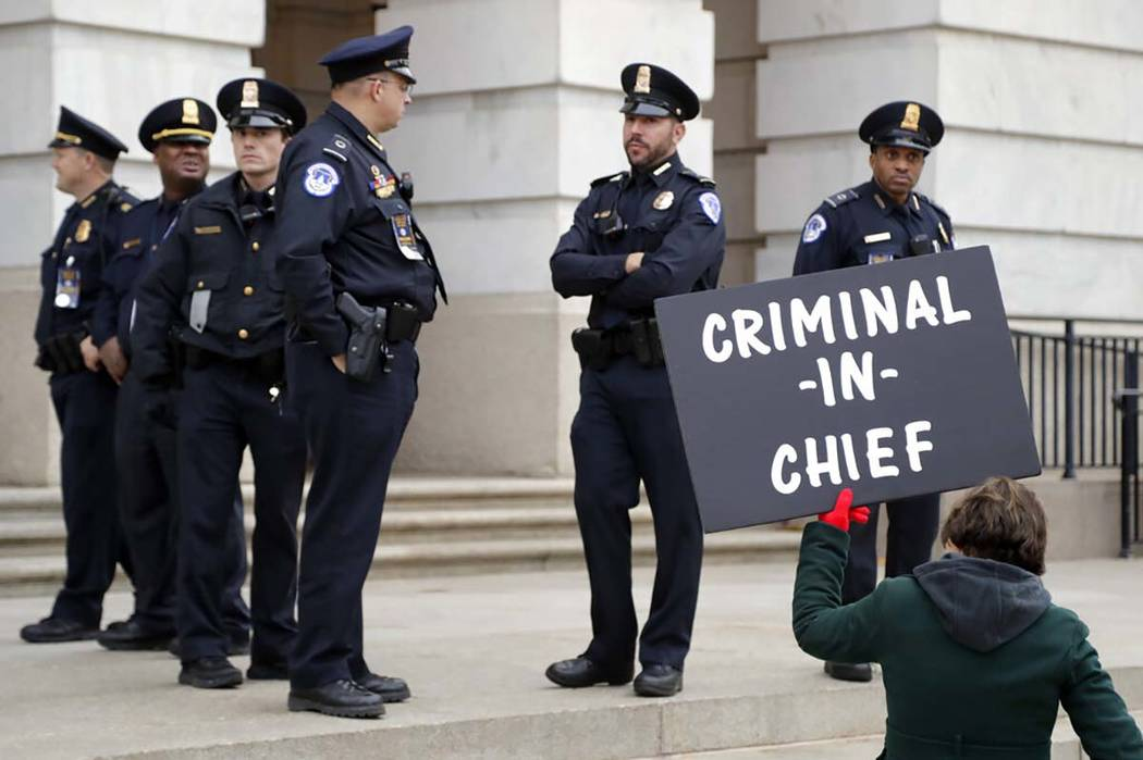 Capitol Police officers stand near a demonstrator holding a sign outside of Longworth House Off ...