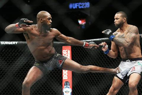 Jon Jones, left, lands a kick against Thiago Santos in the fourth round during their light heav ...