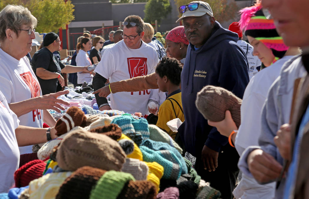 Crowds of people pick out hats and toiletry items at Project Homeless Connect at the Champion C ...