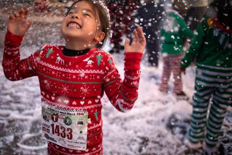 Sydney Buy, 6, of Las Vegas, plays in the fake snow at the seventh annual PJ 5K & 1-Mile Walk o ...