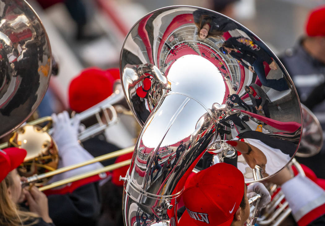Fans and band members are reflected in a tuba as the UNLV band performs during the fourth quart ...