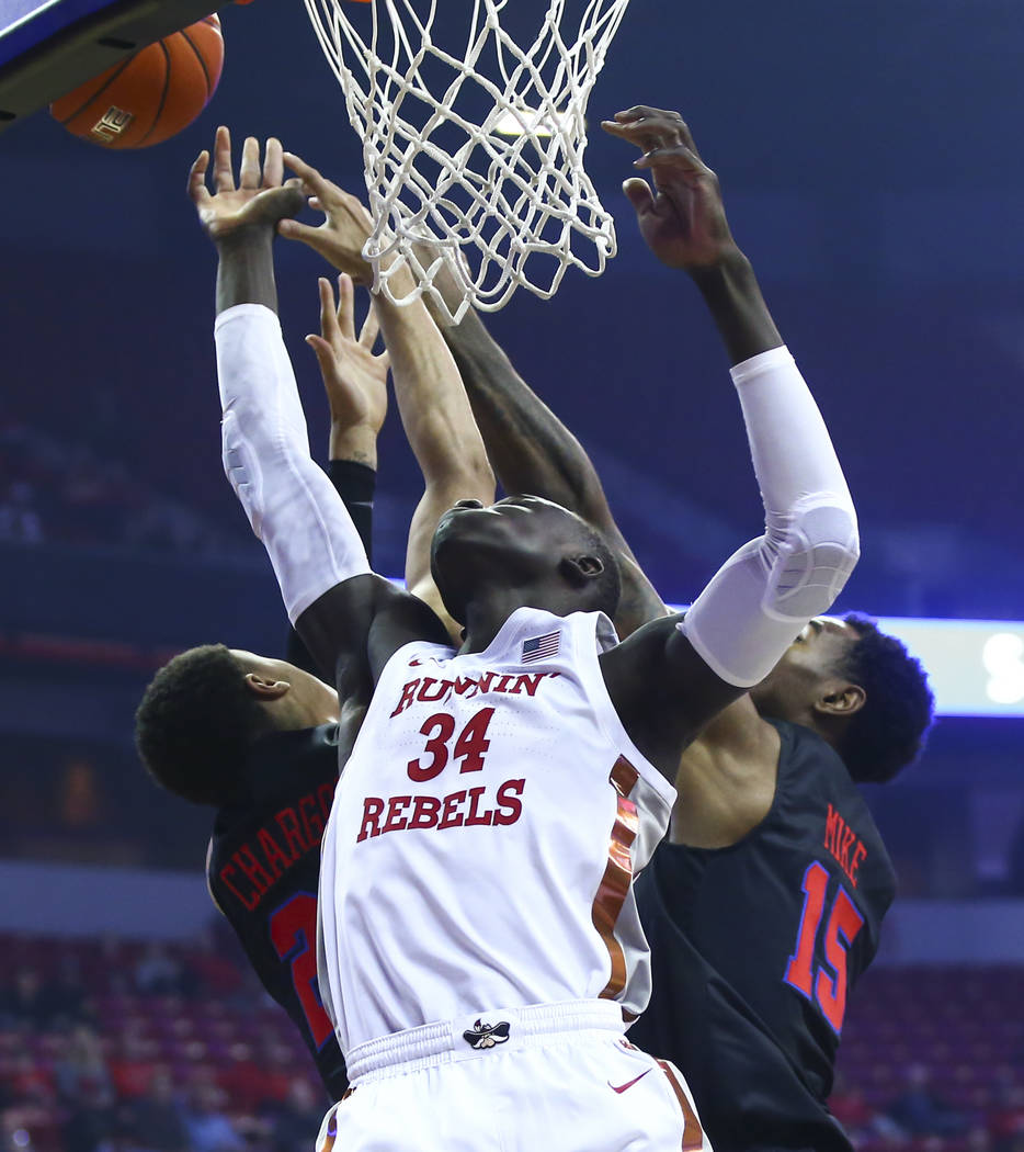 UNLV's Cheikh Mbacke Diong (34) battles for a rebound against Southern Methodist's Ethan Chargo ...