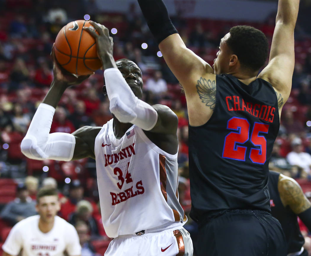 UNLV's Cheikh Mbacke Diong (34) looks to shoot past Southern Methodist's Ethan Chargois (25) du ...
