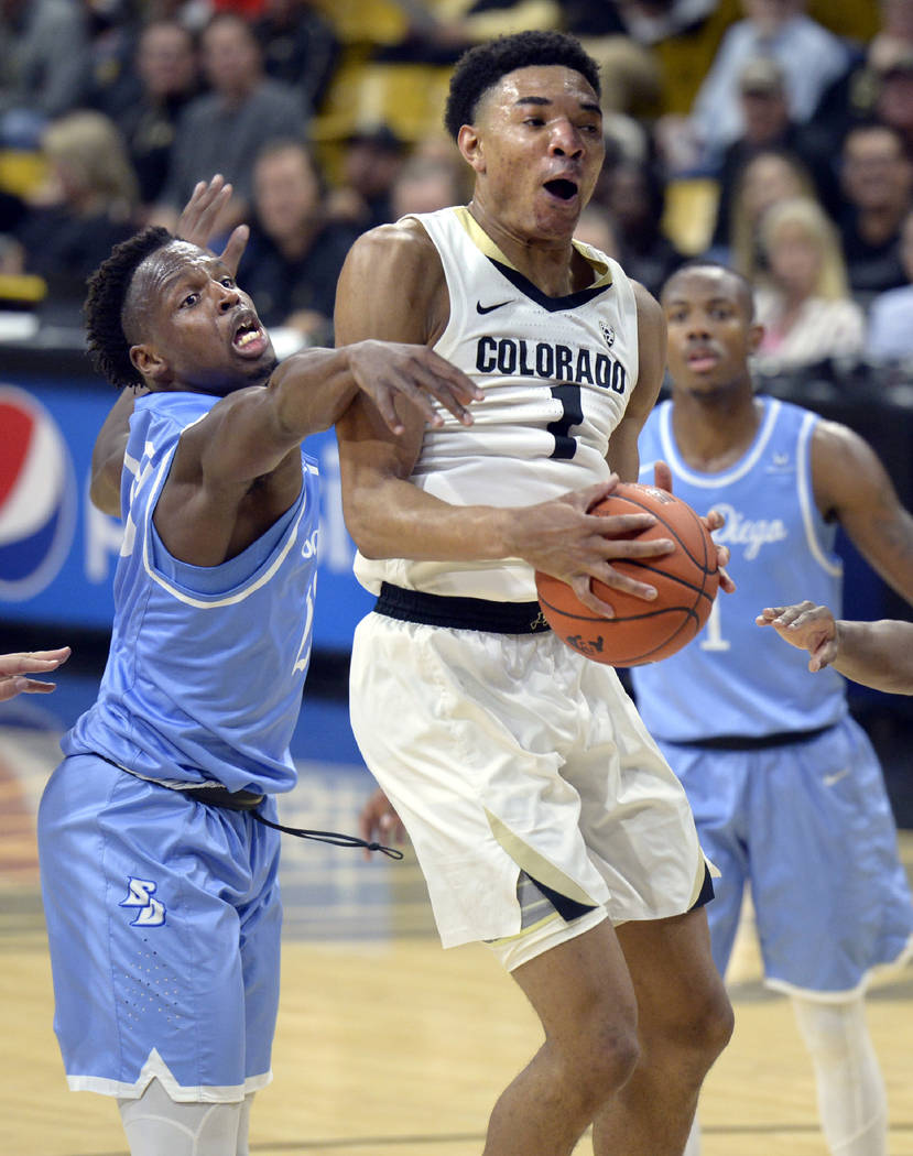 Colorado guard Tyler Bey, right, pulls in a rebound as San Diego center James Jean-Marie defend ...