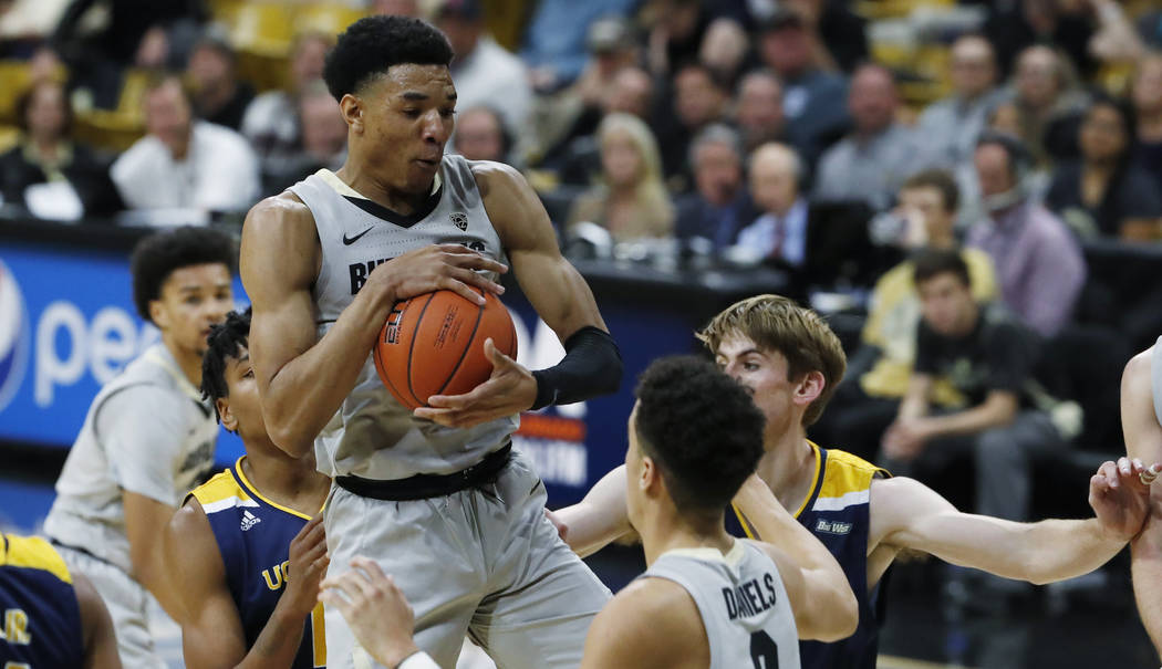 Colorado guard Tyler Bey pulls in a rebound in front of UC Irvine forwards Austin Johnson, back ...