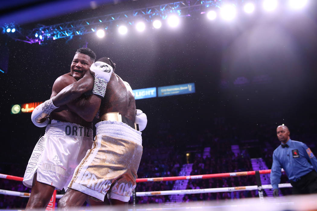 Luis Ortiz, left, smirks as he holds on to Deontay Wilder during the seventh round of the WBC h ...