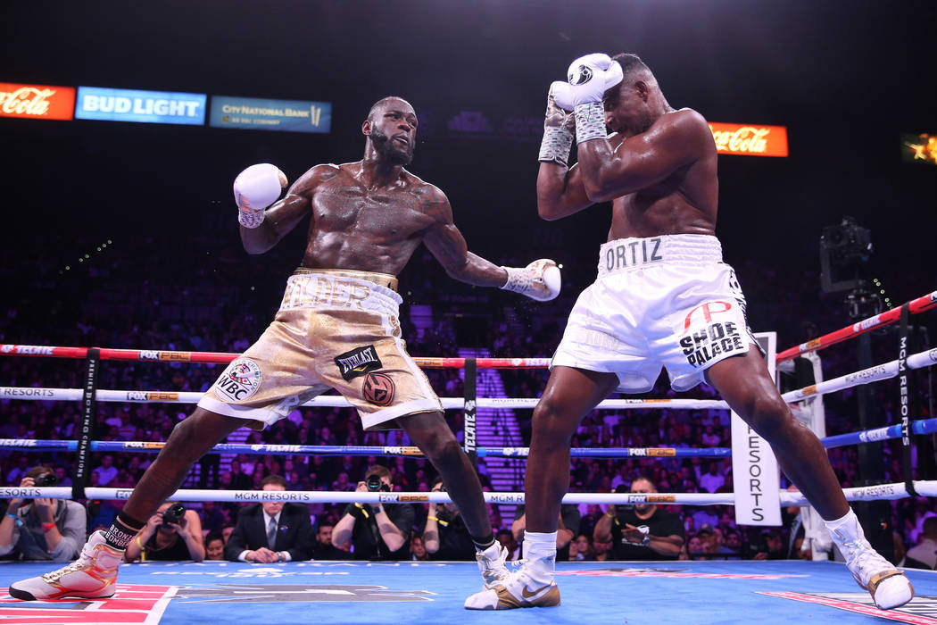 Deontay Wilder, left, battles Luis Ortiz during the seventh round of the WBC heavyweight title ...