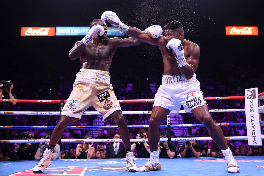 Deontay Wilder, left, battles Luis Ortiz during the sixth round of the WBC heavyweight title bo ...