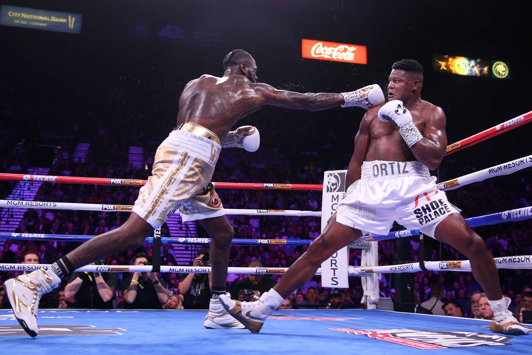 Deontay Wilder, left, throws a punch against Luis Ortiz during the fifth round of the WBC heavy ...