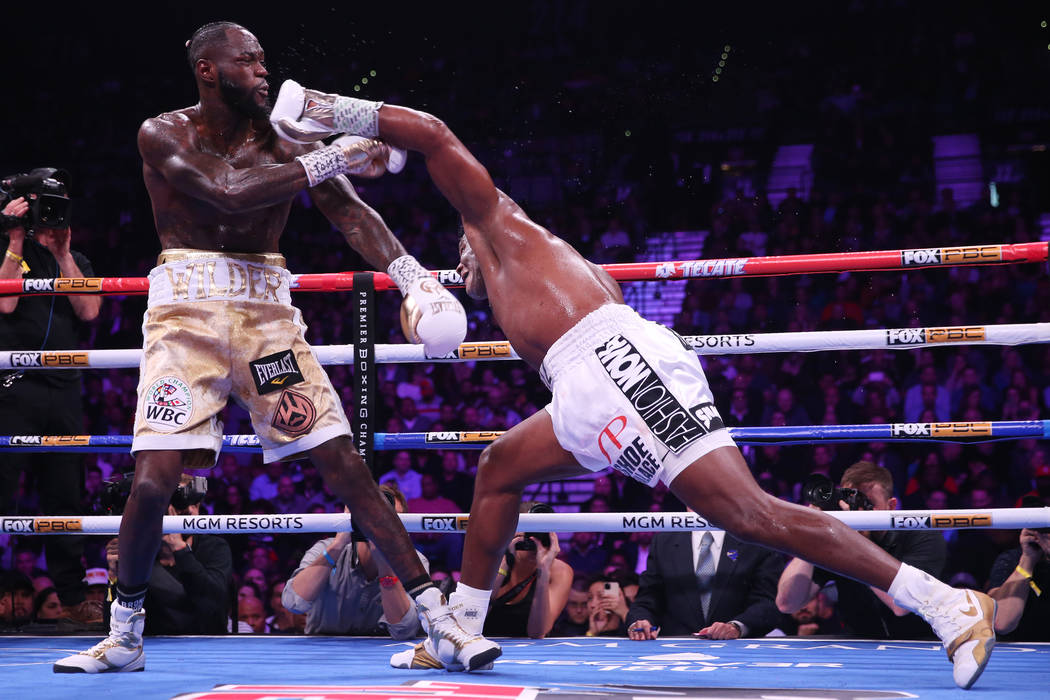 Luis Ortiz, right, throw a punch against Deontay Wilder during the fifth round of the WBC heavy ...