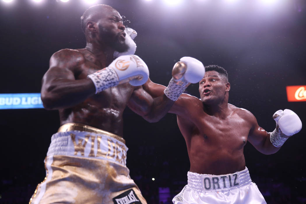 Luis Ortiz, right, lands a punch against Deontay Wilder during the third round of the WBC heavy ...
