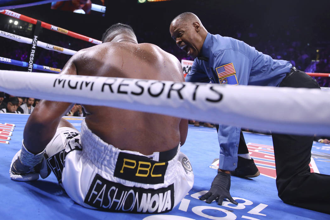 Kenny Bayless gives a countdown to Luis Ortiz after he was knocked down by Deontay Wilder durin ...