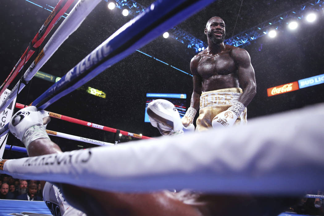 Deontay Wilder, top, stands over Luis Ortiz after knocking him down during the seventh round of ...
