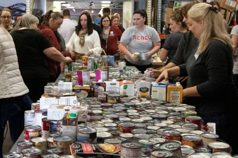 """Attendees of The """"Done in a Day"""" event fill approximately 2,500 bags of donated food ..."""